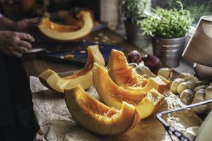 Cutting a fresh pumpkin into slices in a rustic kitchen.