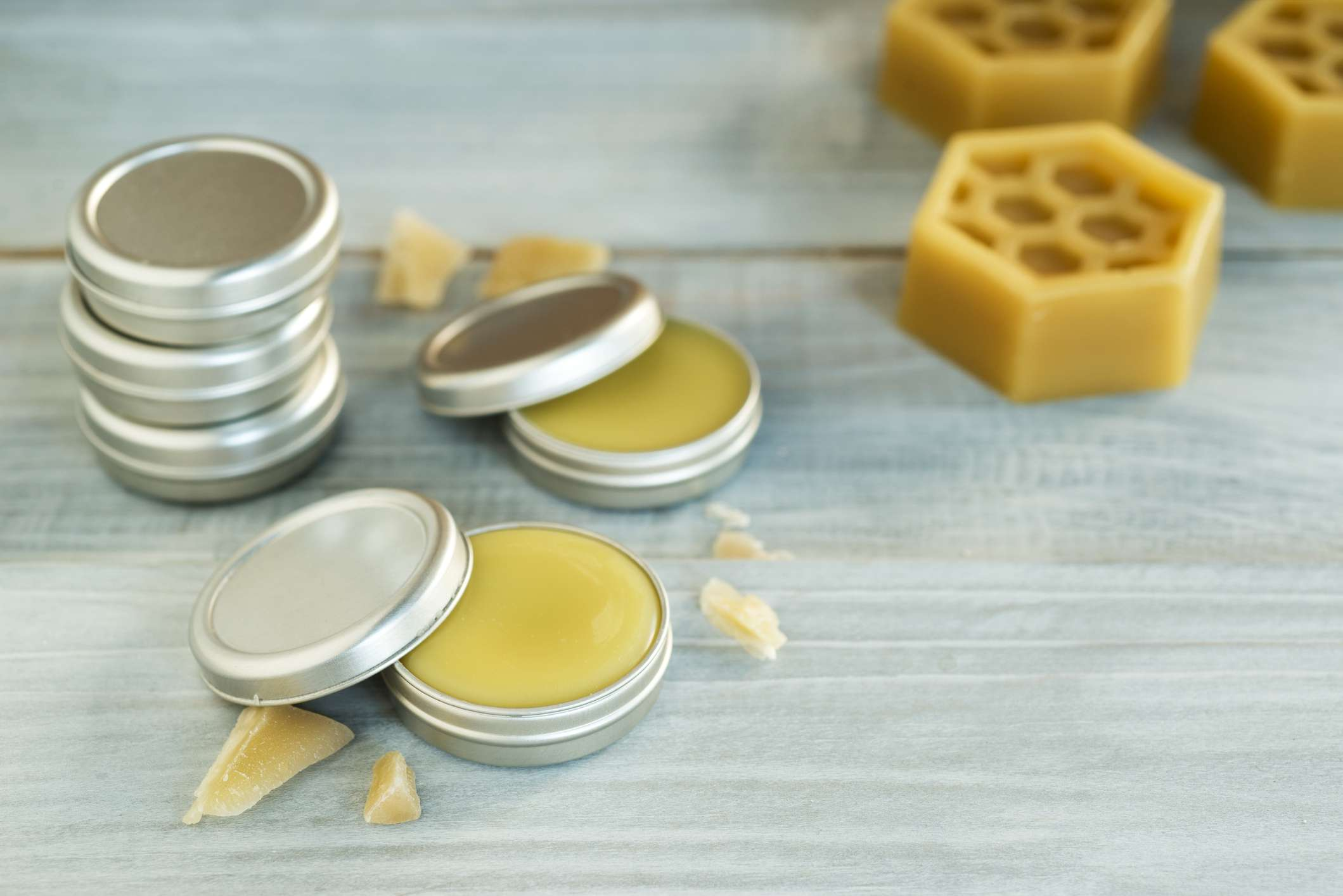 Tins of homemade lip balm on wooden table background.