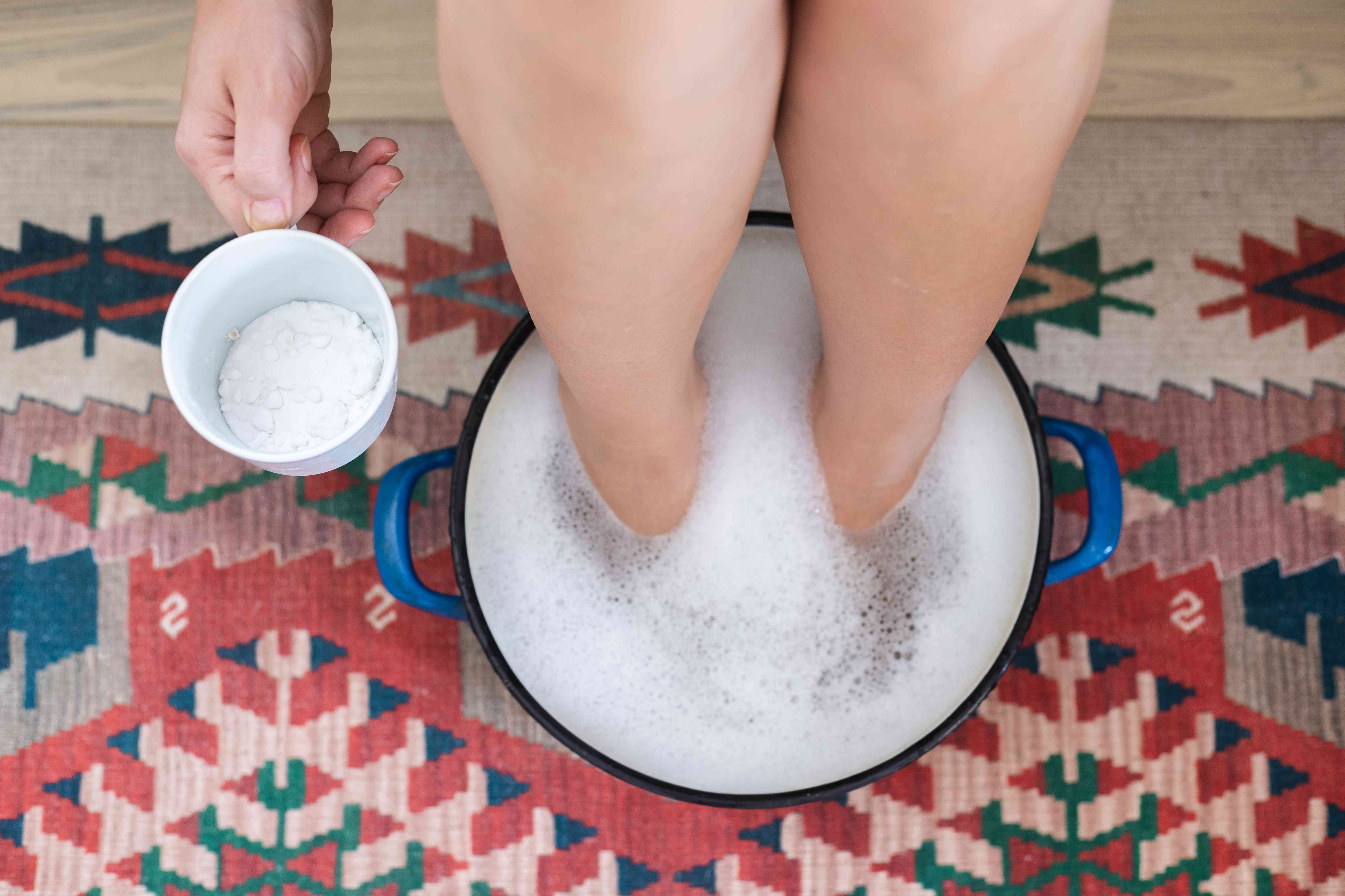 feet soak in large soup pot filled with hot water while person holds cup of baking soda