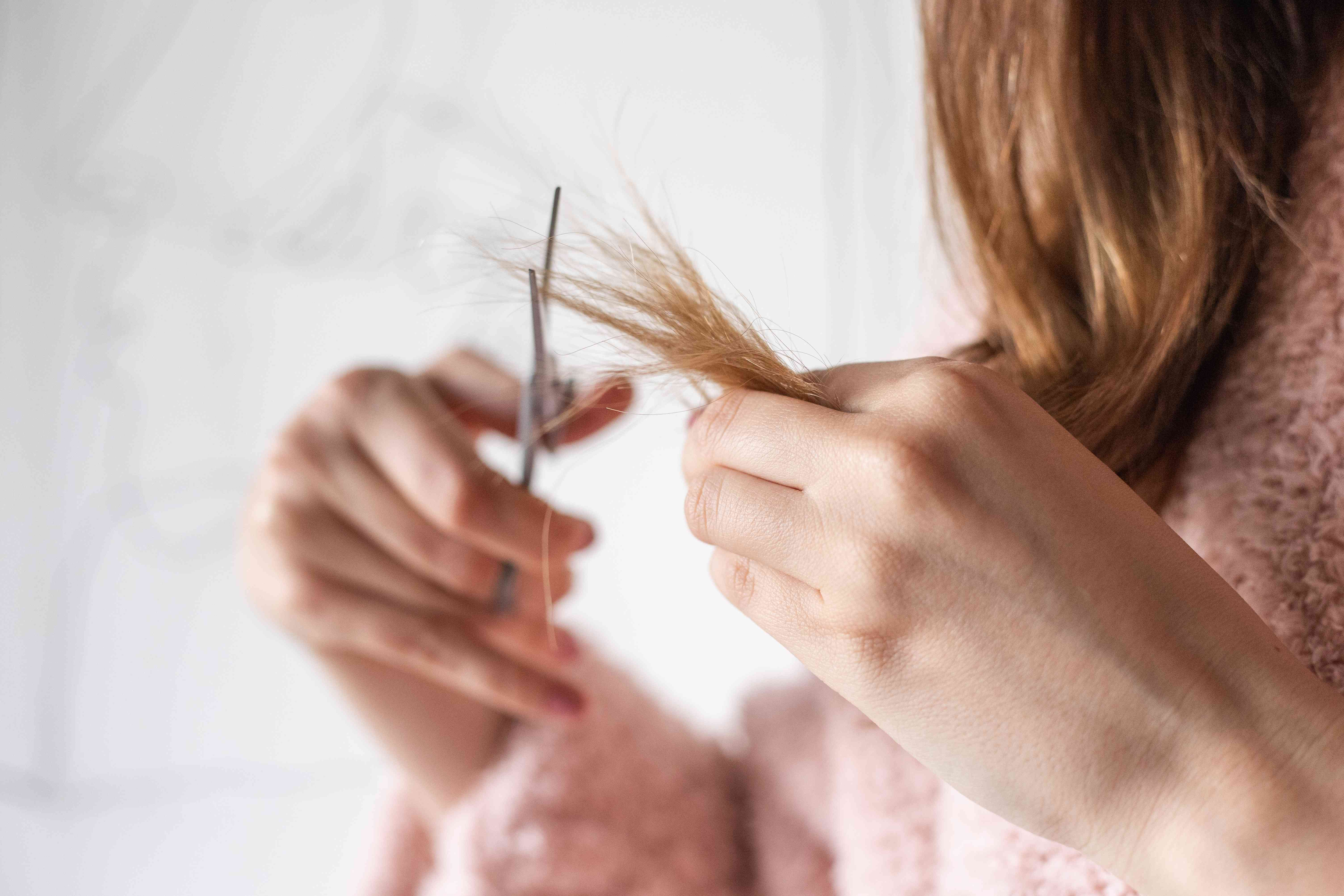 person in pink sweater holds ends of hair and trims with scissors in other hand