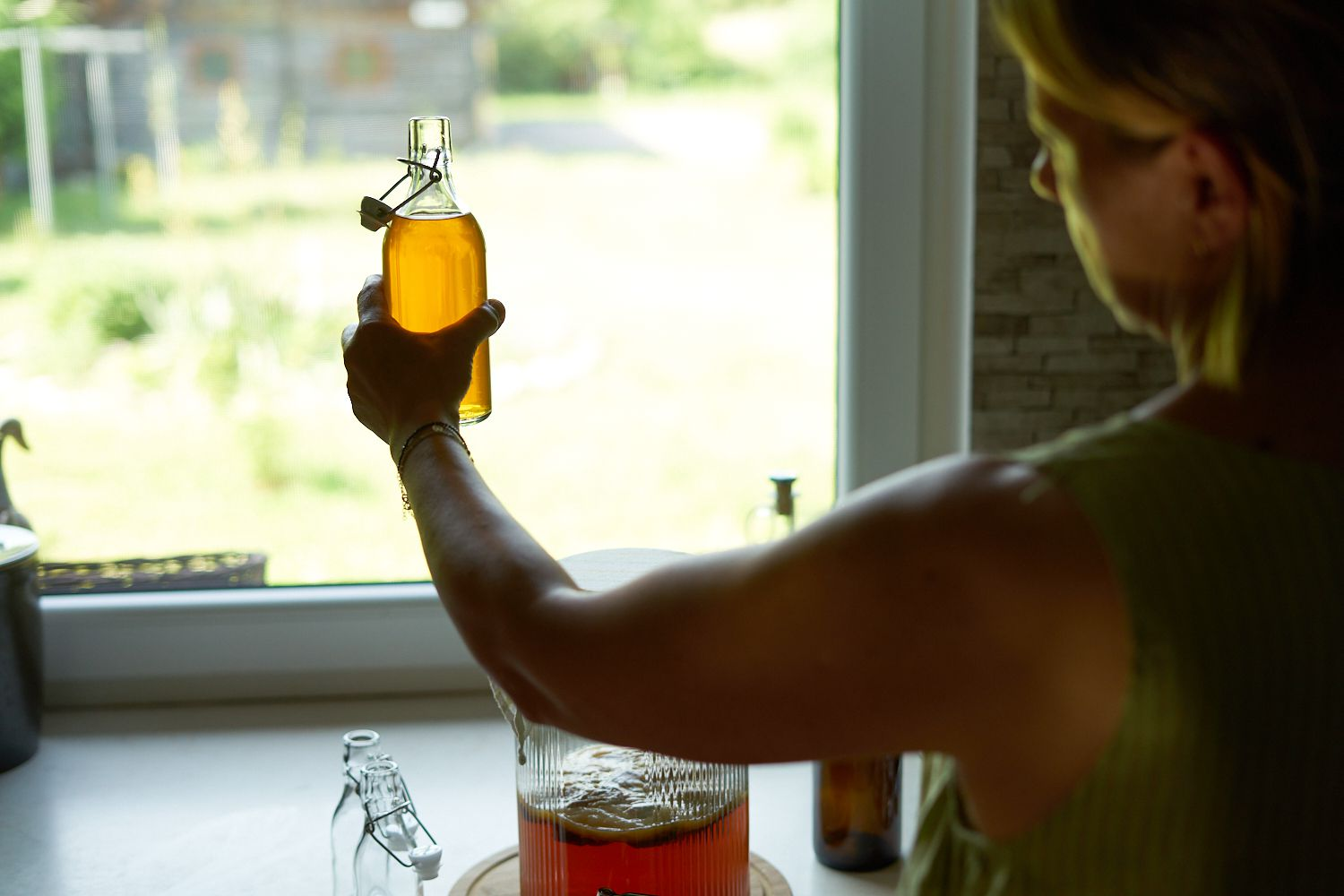 woman holds homemade kombucha in flip-top glass container up to kitchen window