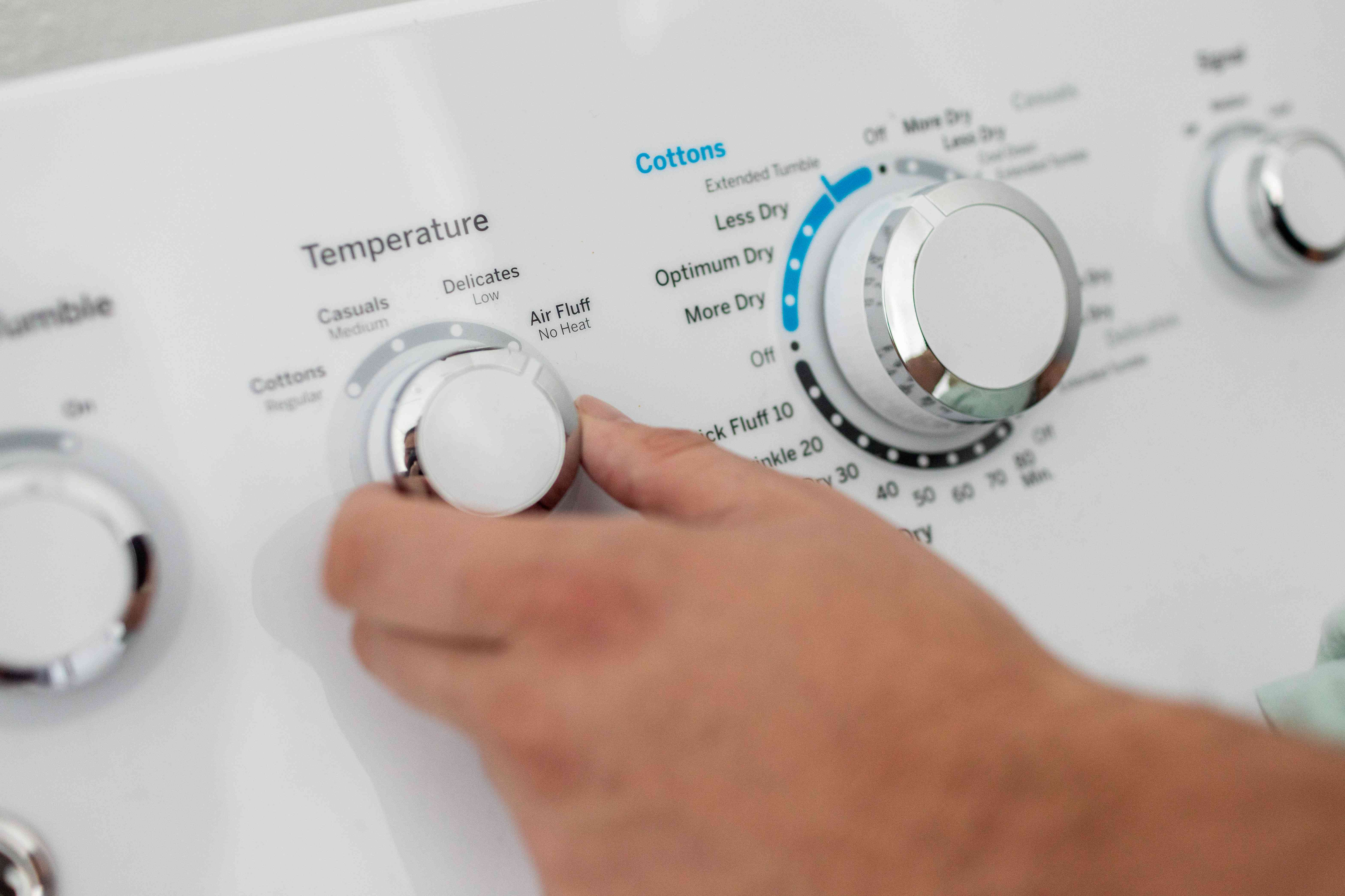 hand turns dial on clothing dryer to air fluff option for pillows