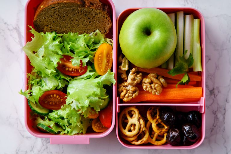 Lunchbox with a salad, bread, apple, veggies, nuts, and pretzels