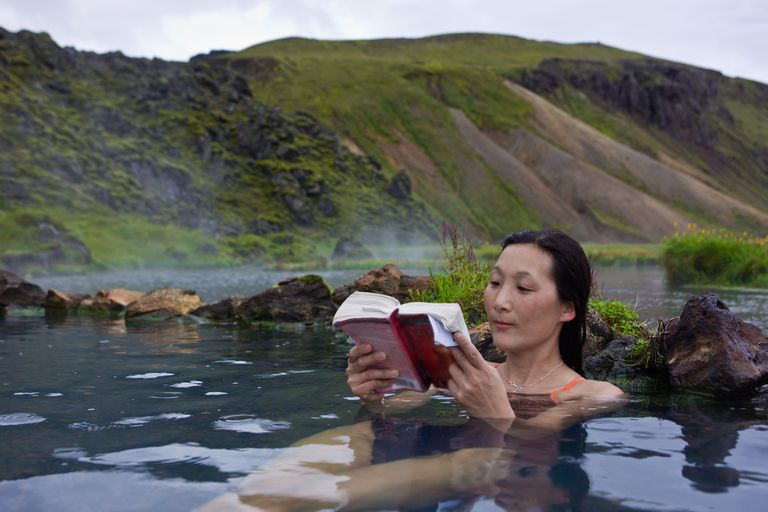 woman reading book in thermal pool at Landmannalaugar, Iceland