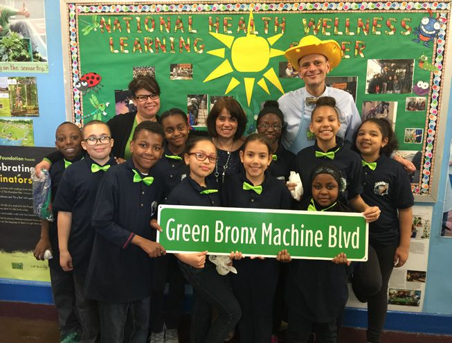 Stephen Ritz poses with students holding a sign for Green Bronx Machine