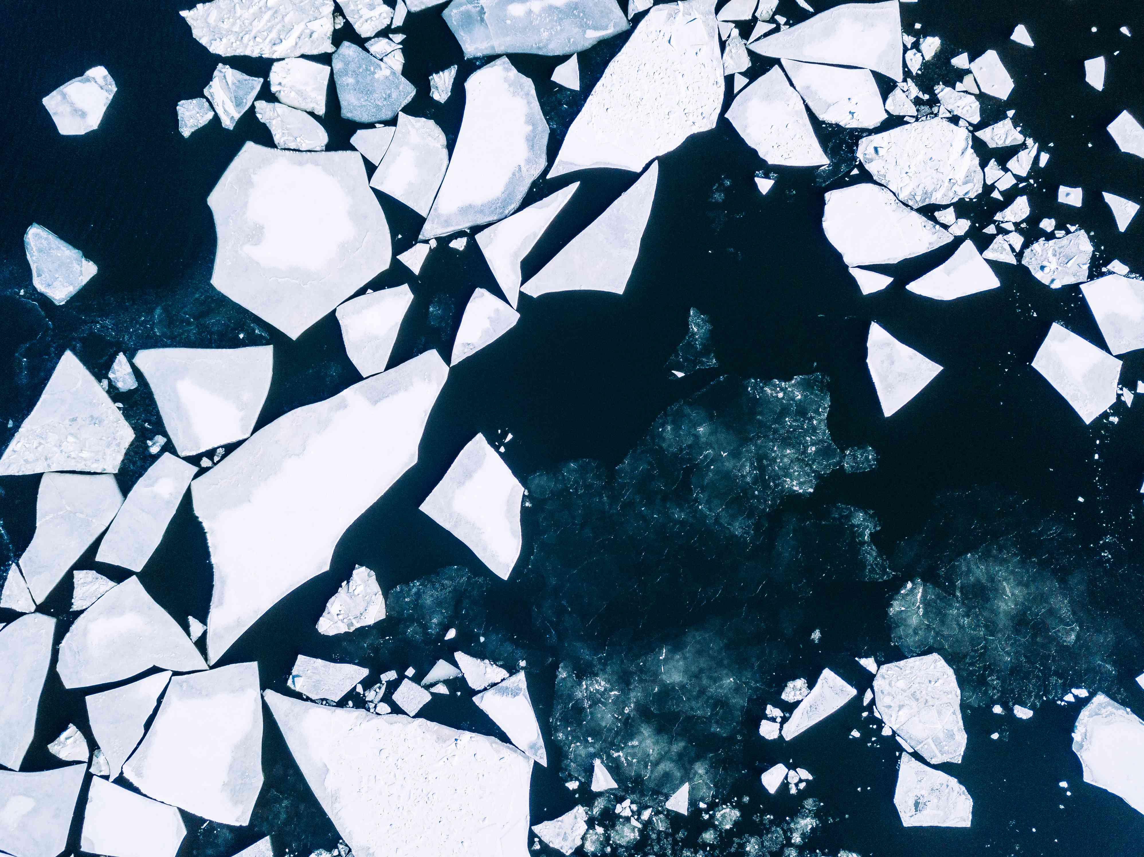 Wintery top-down aerial view of cracked ice on Baltic Sea around Helsinki