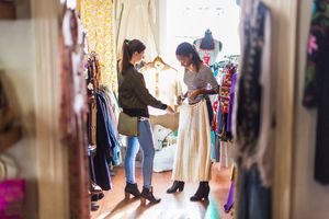 Two young women looking at clothes in a vintage clothes shop