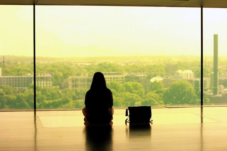 Person sitting at a large window wall looking out