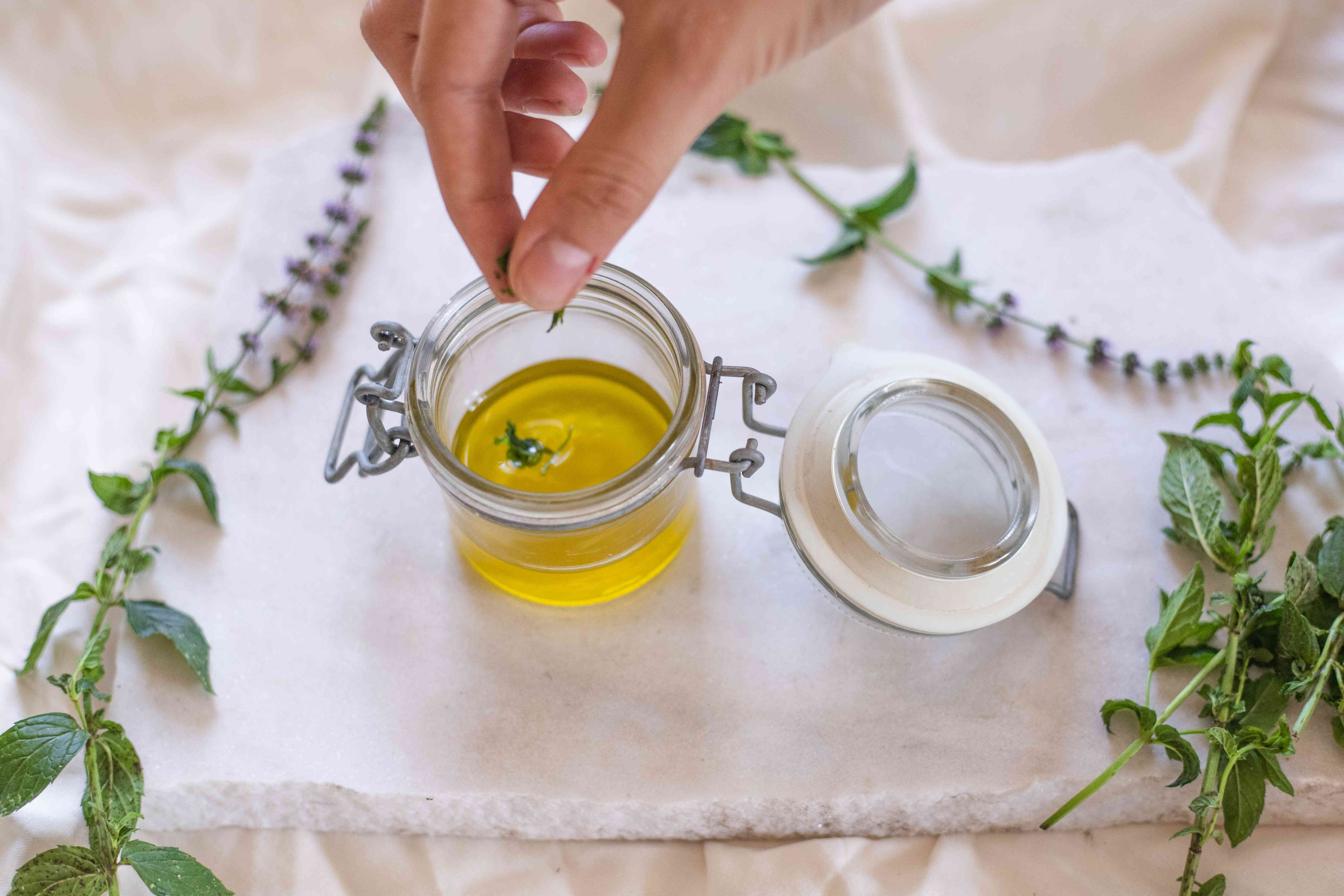 melted olive oil hair mask with fresh herbs being added to glass flip lid container