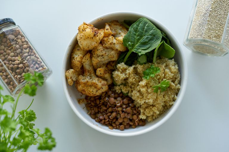 overhead shot of grain bowl with cauliflower and spinach in white bowl on white backdrop