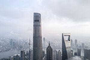 Tall silver skyscrapers against a foggy sky