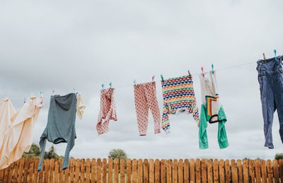Clothes hanging outside on a line in front of a picket fence.
