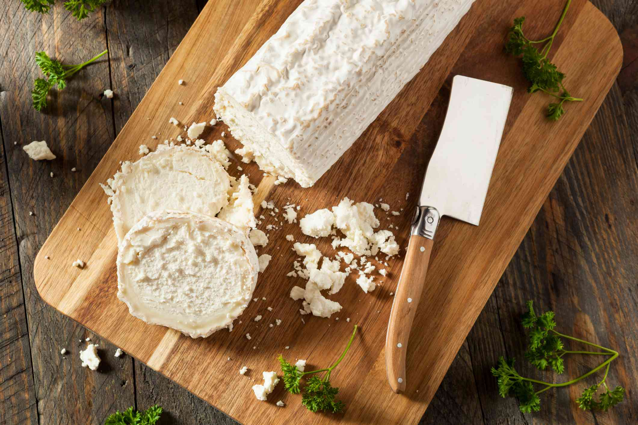 Goat cheese on a cutting board with a knife.