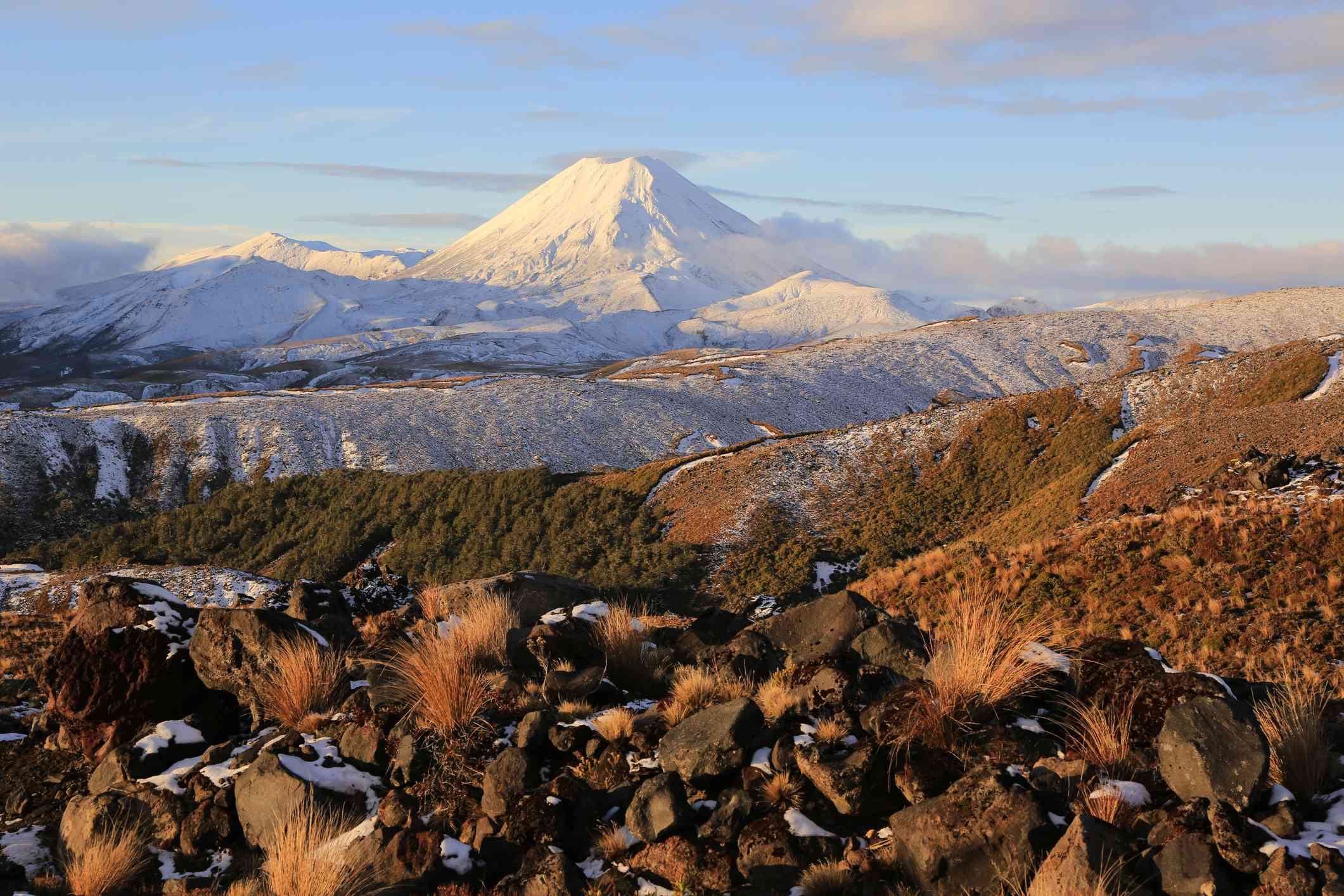 Active volcanoes of Mt Ngaruhoe and Mt Tongariro covered in snow from base of Mt Ruapehu, covered in rocks, Tongariro National Park, New Zealand