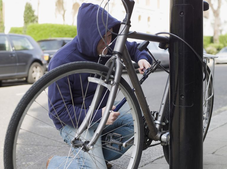 A man trying to cut a lock off of a bike.