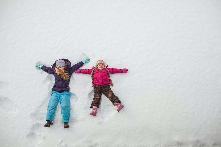 little girls make snow angels