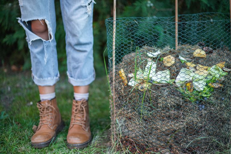 woman in ripped jeans stands next to diy cold compost frame outside in yard