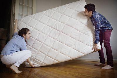 Man and woman moving a mattress