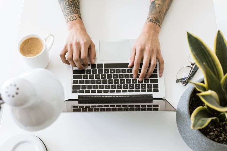 Hands with tattooed sleeves type on a laptop with coffee and plants.