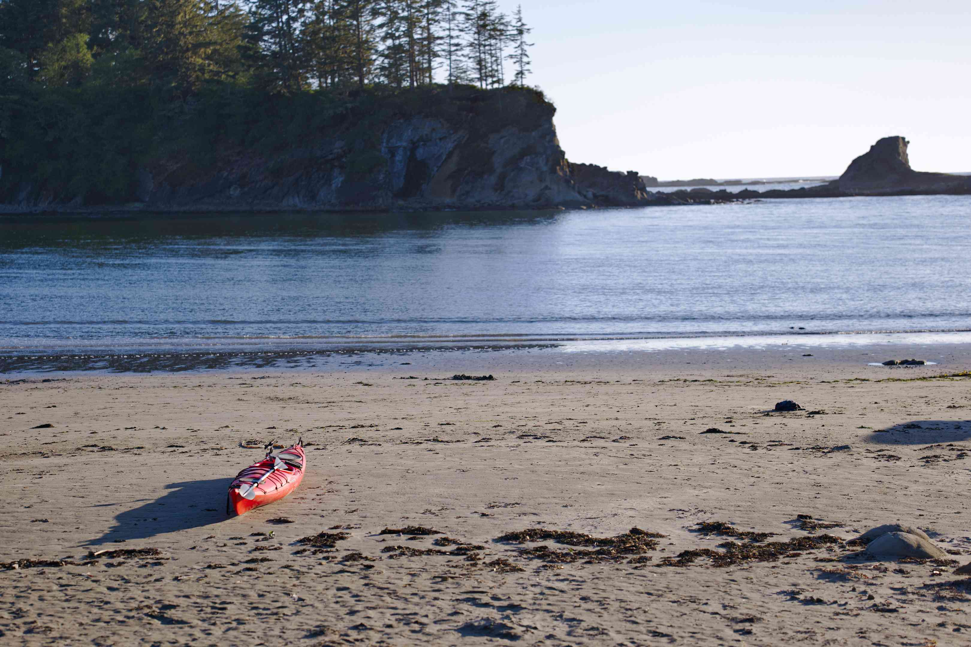single red kayak sits on shore of rocky wooded beach