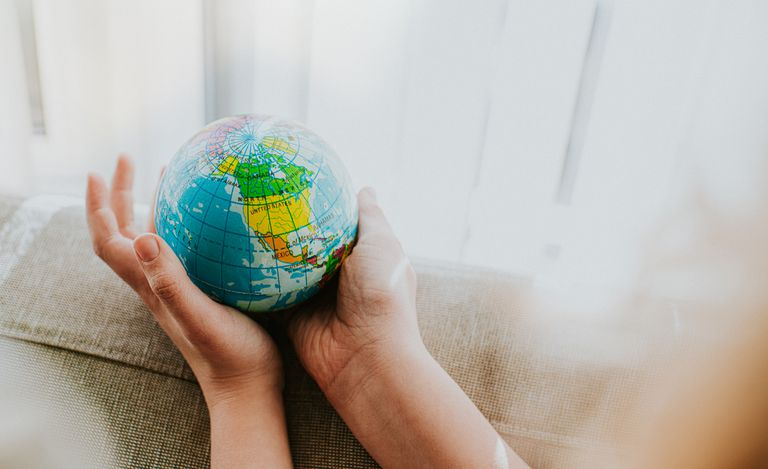 A child's hands holds a globe by a window.