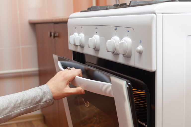 person opening door of a gas stove