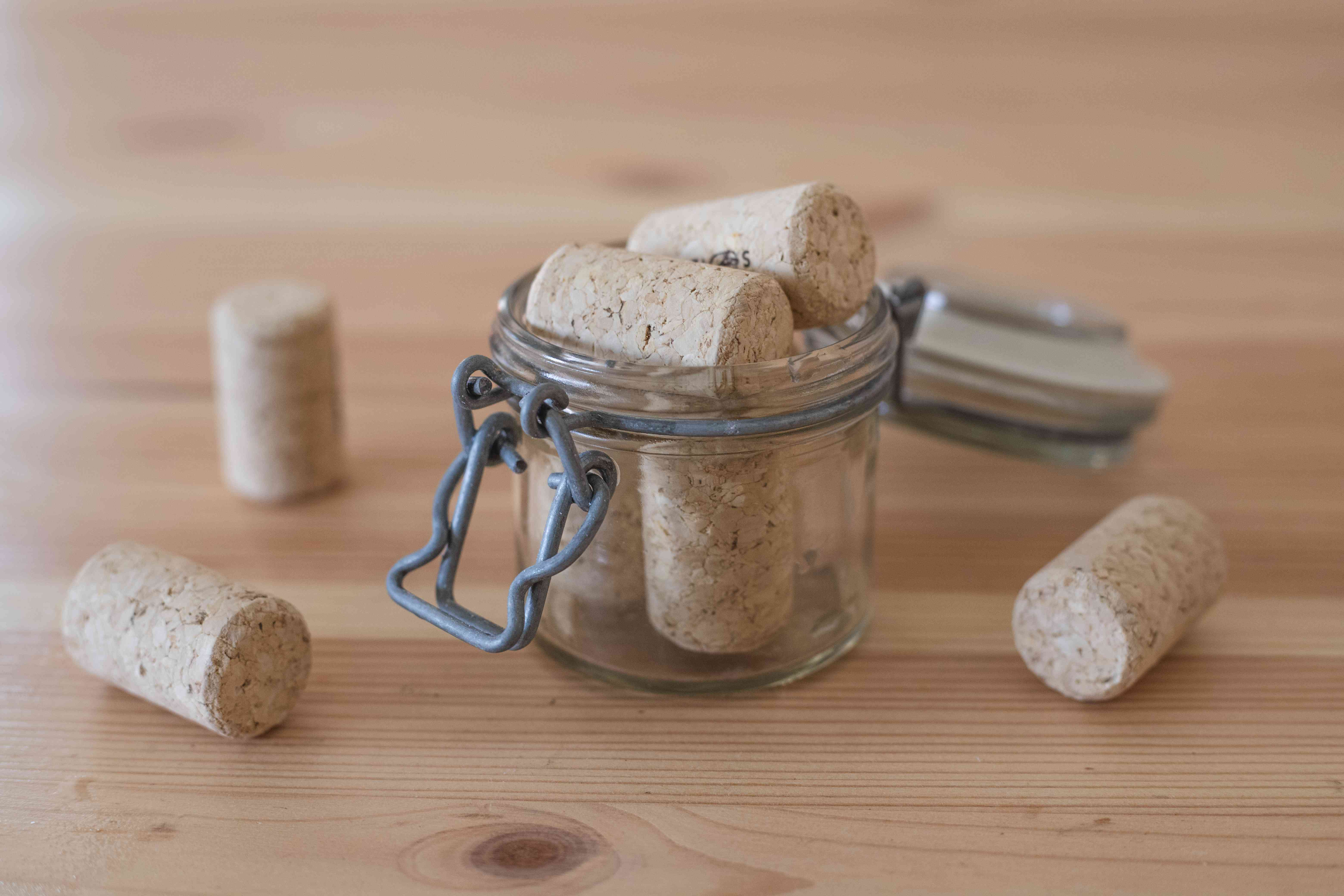 various wine corks scattered on wooden table and in glass jar