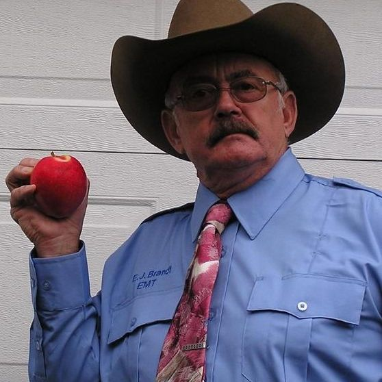 older man wearing a hat shows off his apple