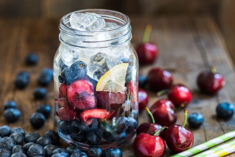 fruit and ice in a mason jar, cherries and blueberries on a table around it