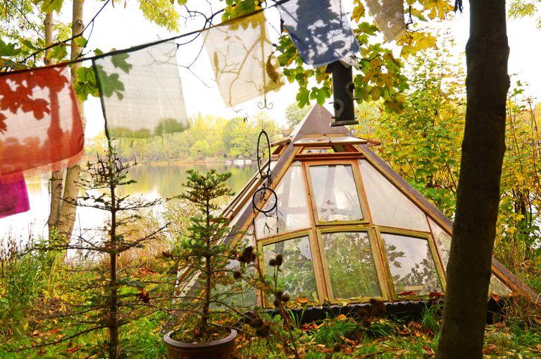 A small triangular glass greenhouse.