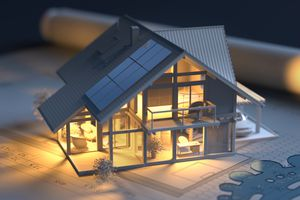 Solar panels on model house with architectural drawing