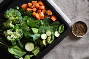 black matte sheet pan with cut broccoli, carrots, and zucchini with bowl of spices
