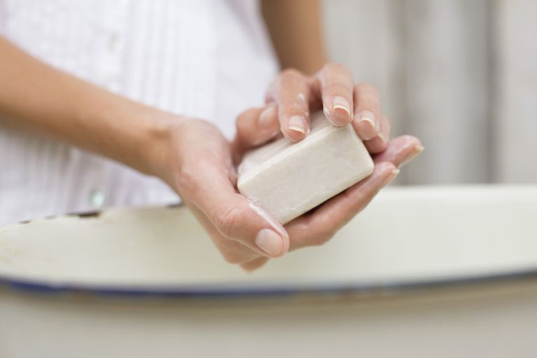 Woman washing her hands with bar of soap.