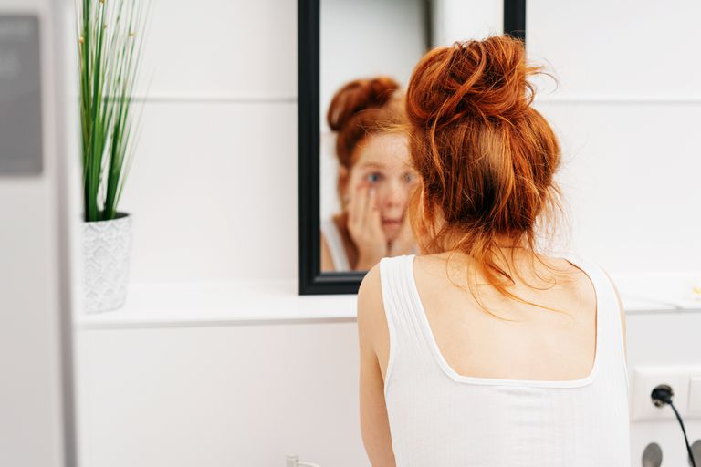Redheaded woman looking at her puffy eyes in the bathroom mirror.