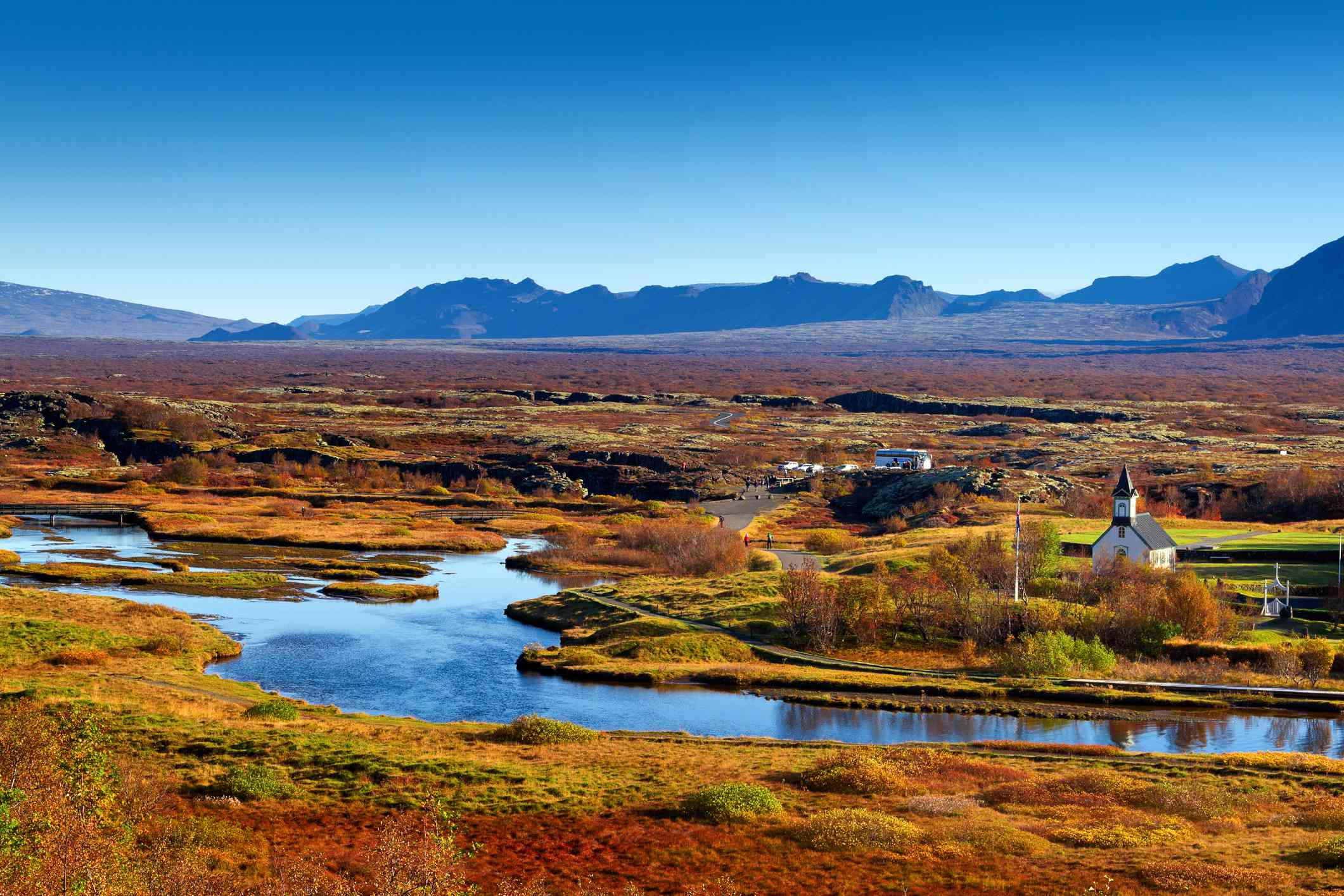 Thingvallakirkja Church along banks of Oxara River in Thingvellir National Park, Iceland, with trees and plants in shades of red, green and orange on both sides of the river, mountains and bright blue sky in the distance