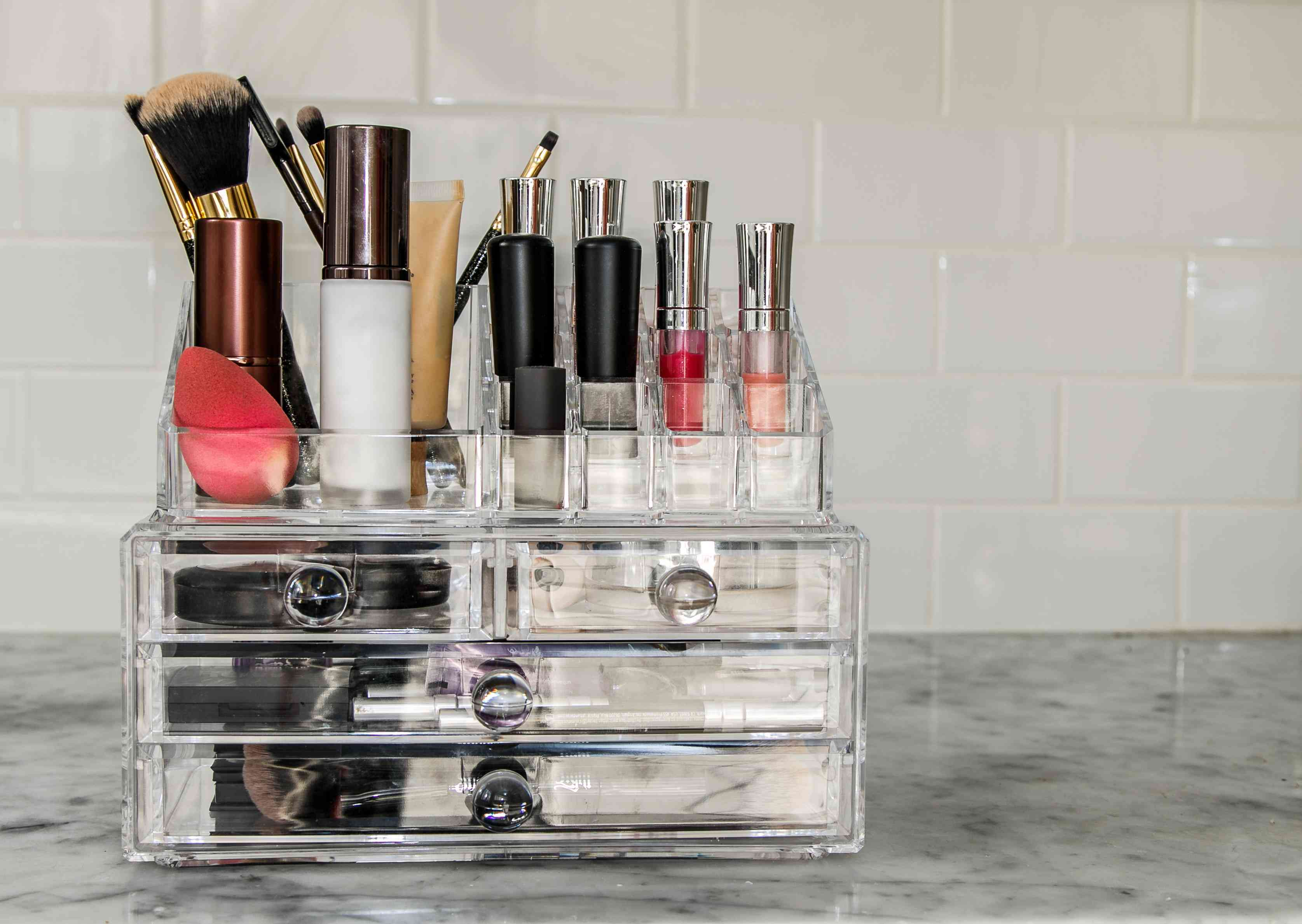 Beauty products, lipstick, brushes, gloss in a plastic organizer.