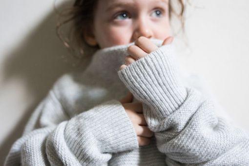 little girl wearing an oversized wool sweater