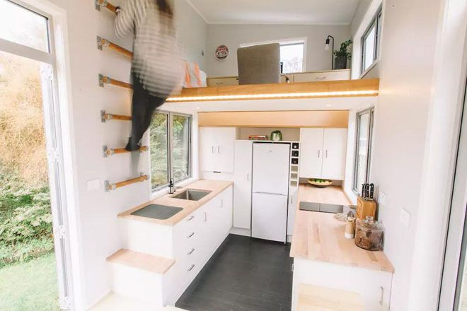 Woman climbing ladder rungs attached to the wall to access the workspace above the kitchen