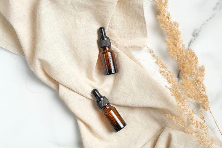 Glass amber jars full of oil for healthy skin.