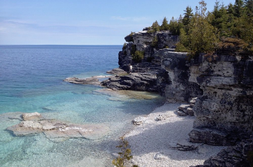 A view of Indian Head Cove, a rocky area covered with trees above the turquoise water of Georgian Bay and Lake Huron