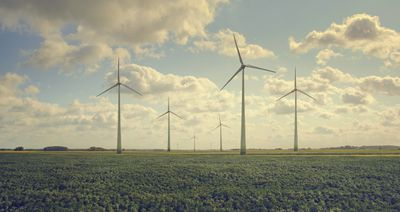flat farmscape filled with wind turbines and cloudy sky
