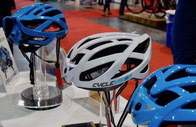 Three Cyclevision helmets sitting on a display, one white and two blue