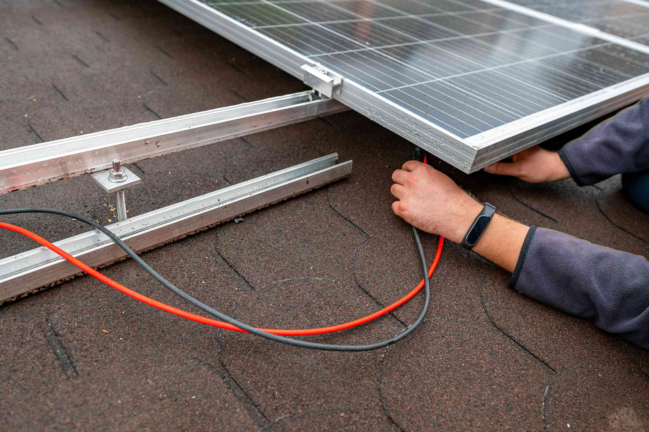 Man Installing solar panels on roof