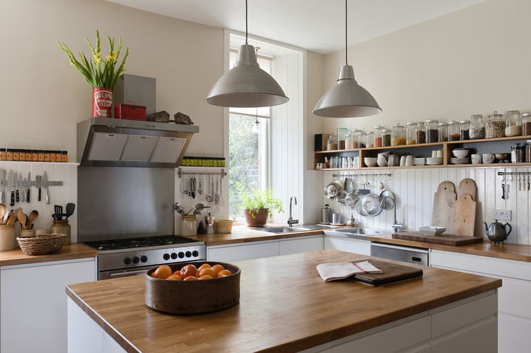 Wood top kitchen island with a bowl of apples on top, and a kitchen counter in the background