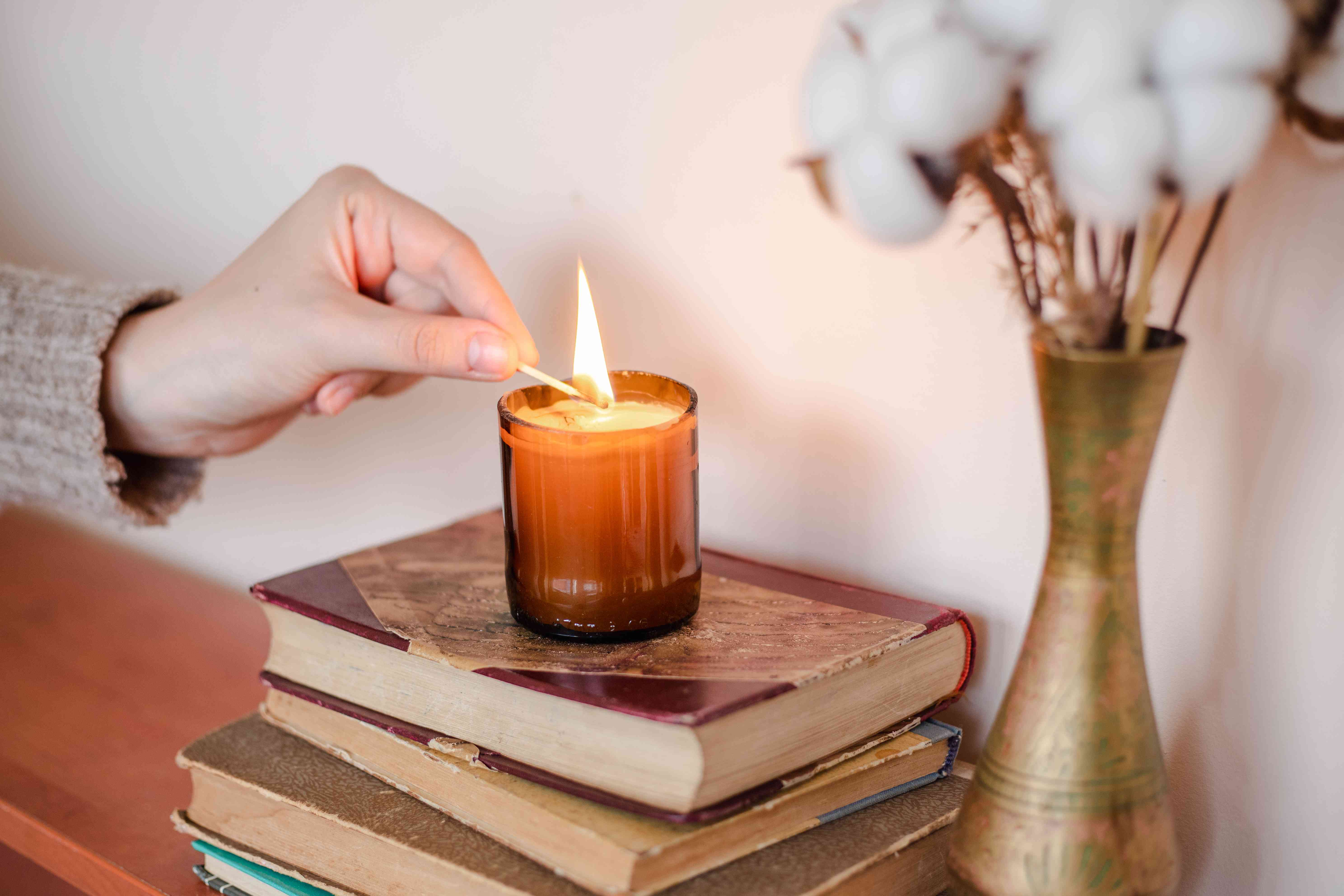person lights candle in upcycled brown wine bottle cut into candle holder on top of books