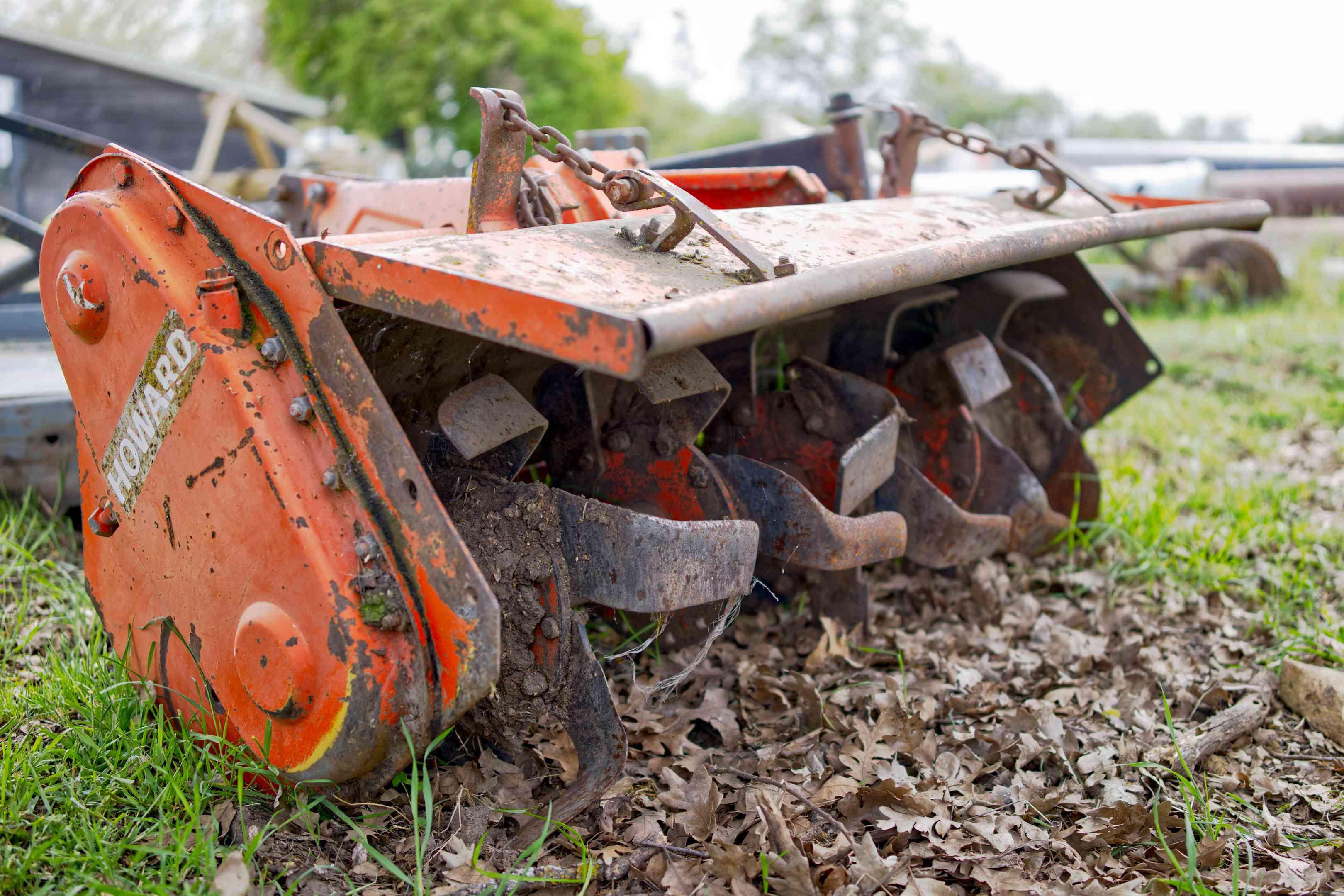 close low-ground shot of orange metal PTO tiller farm equipment breaking up soil