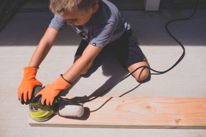 little boy using a sander