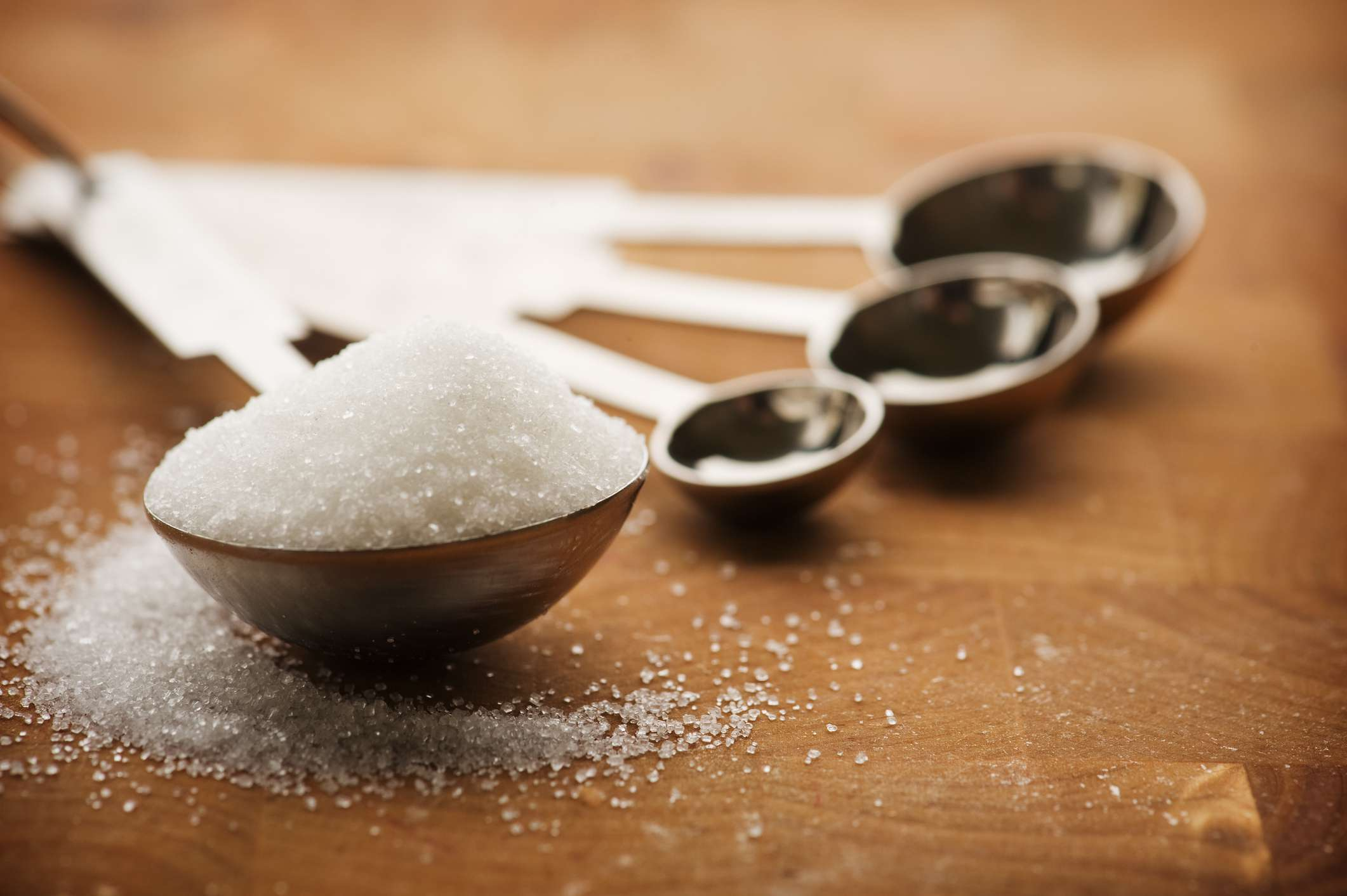 Sugar in a measuring spoon on a wood surface.