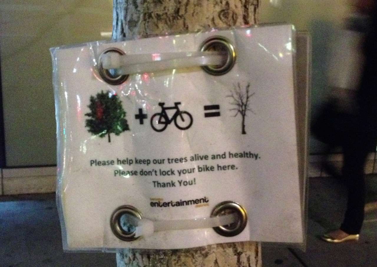 Note tied to tree, asking people not to lock bikes to trees