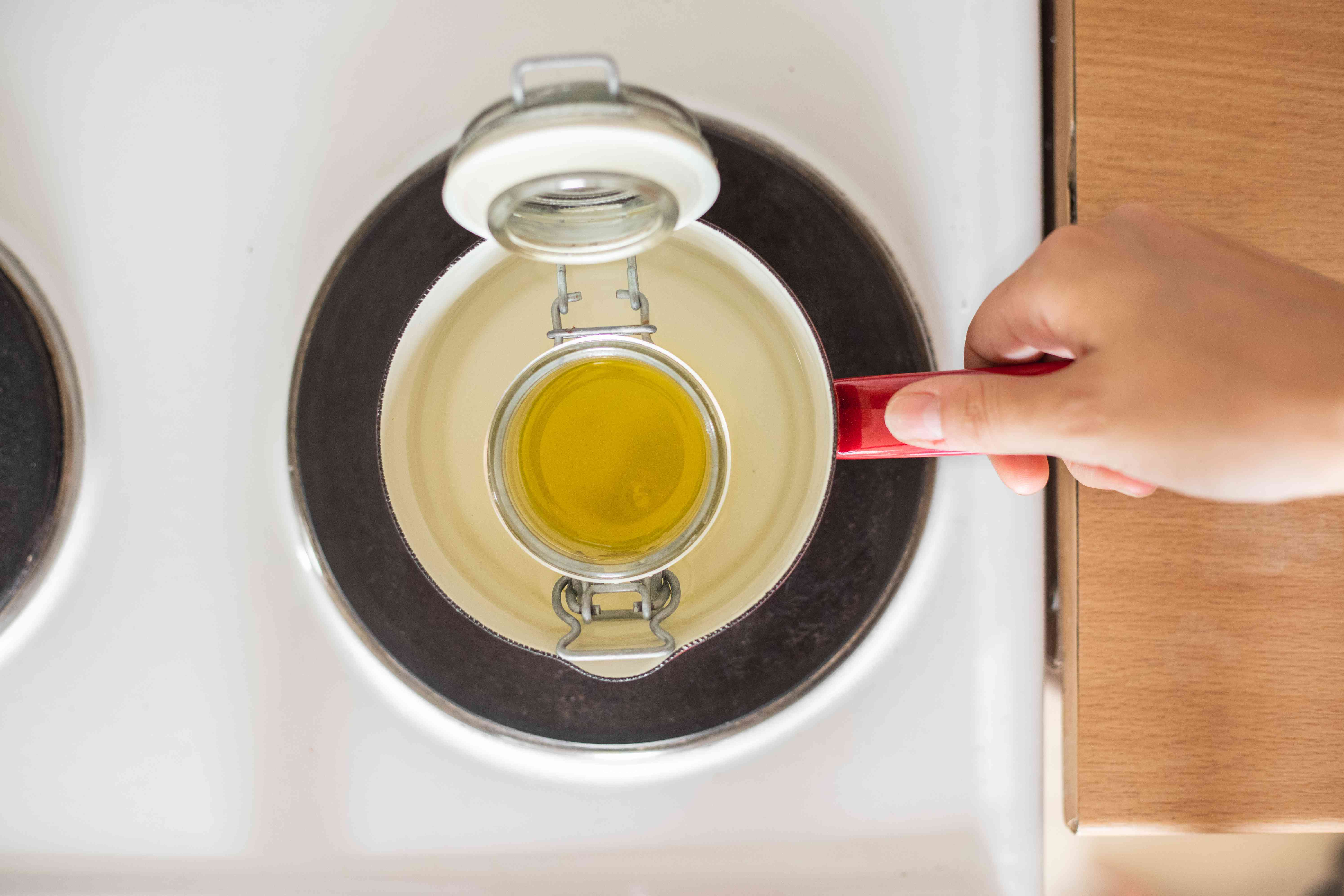 hand heats olive oil in glass container on electric stove